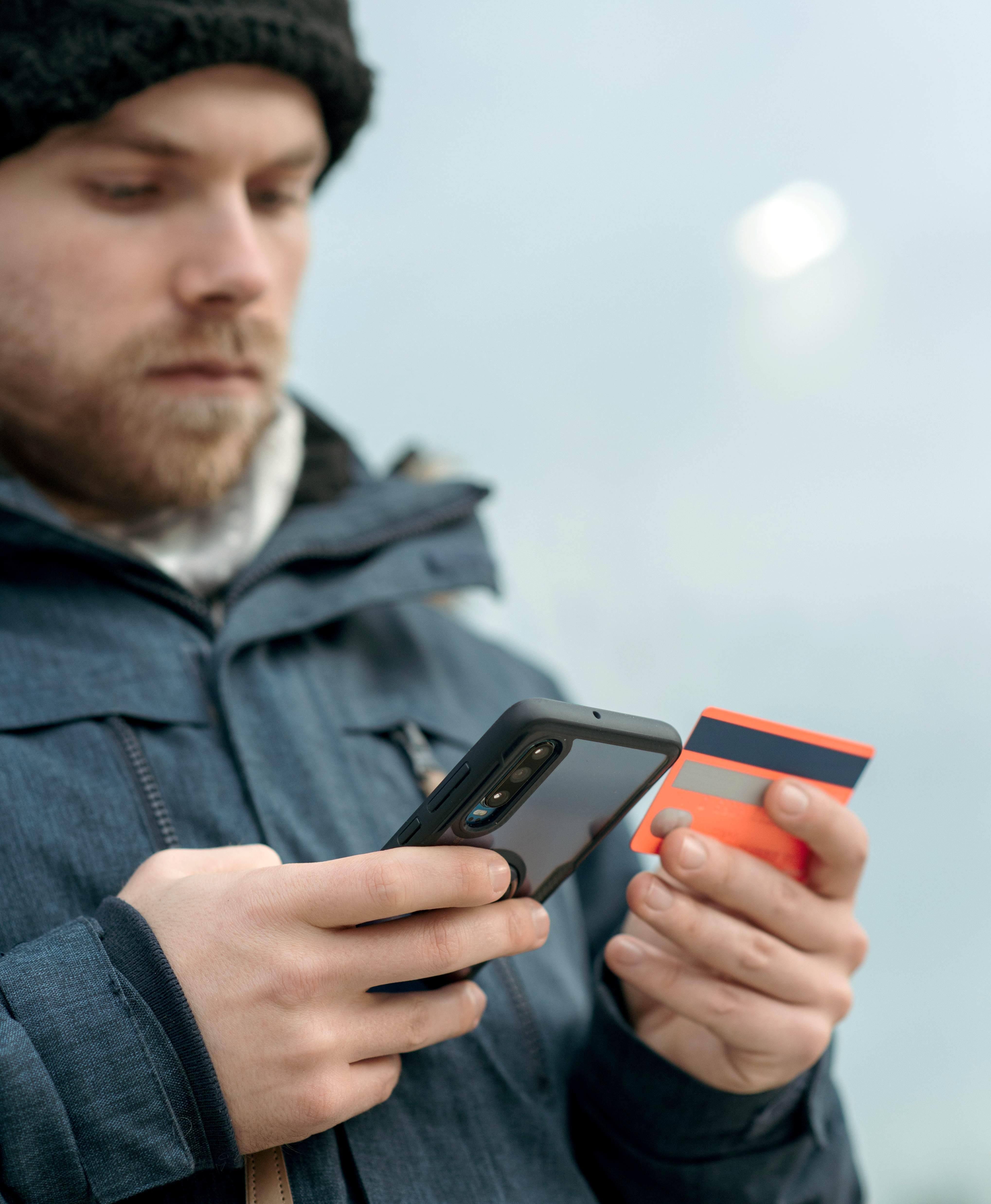Persona che usa le app su smartphone e tiene in mano una carta bancaria - Abaco Mobility